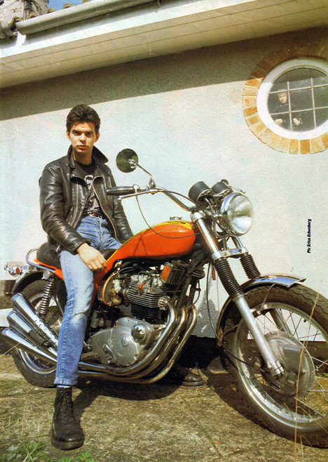JJ Burnel in Black Leather Jacket and Doctor Martens Boots aboard a Triumph Hurricane Triple