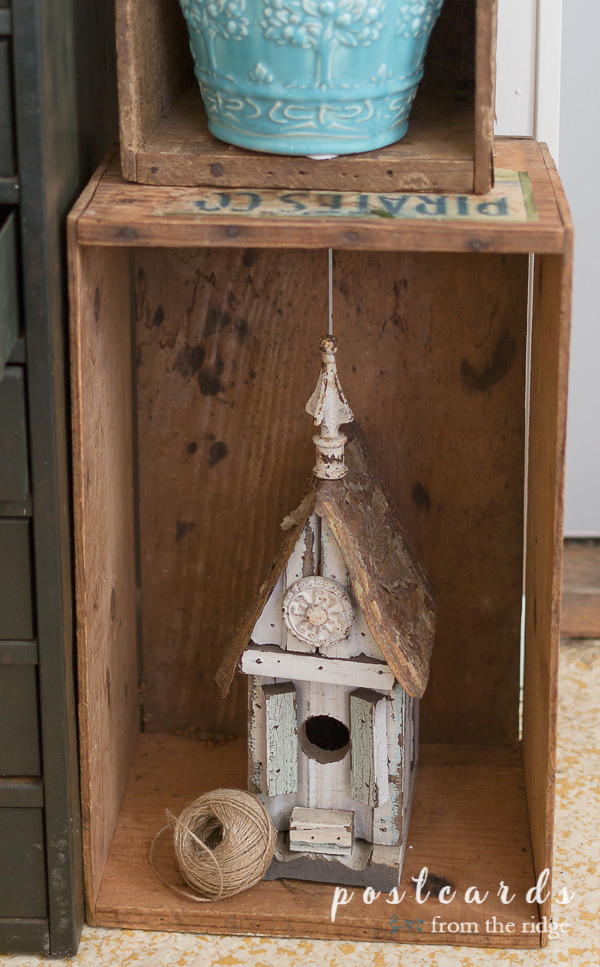 rustic birdhouse in old wooden crate used as cottage garden decor