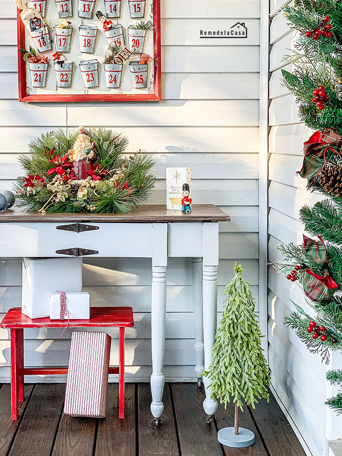 Front porch decorated for Christmas with painted antique table and decor