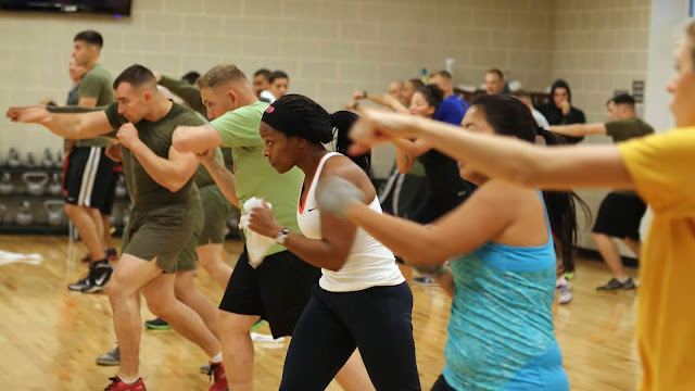 A group of people exercising. It looks as though they are throwing punches.