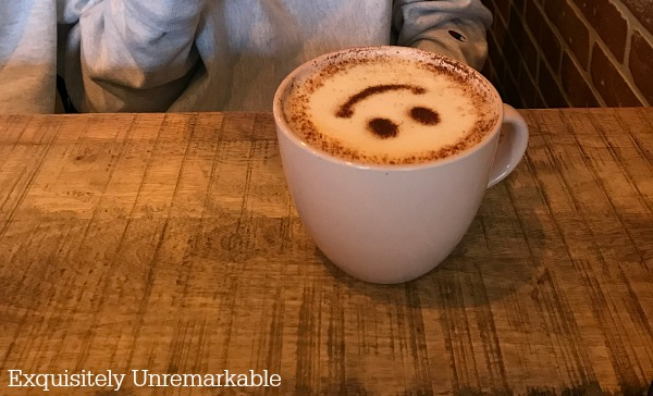 Happy face made on coffee in a white mug on a table