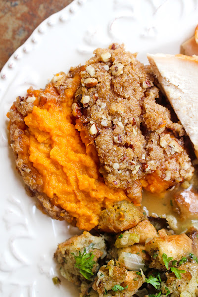 Top view of a scoop of brown sugar pecan sweet potato casserole in a plate with stuffing.