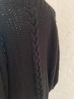 zwart vest gebreid met vlechtkabel op de rug