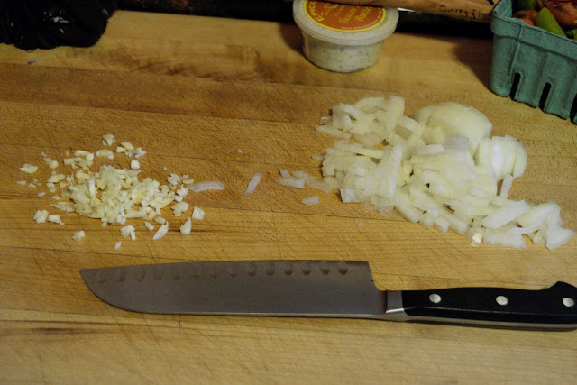 The diced onion and minced garlic on a cutting board with a knife below it.