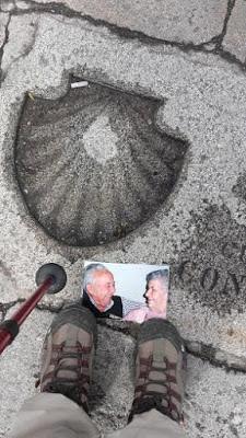 um bastão de peregrinos, dois pés e uma foto de um casal