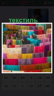 на улице на веревках сушится текстиль различного цвета