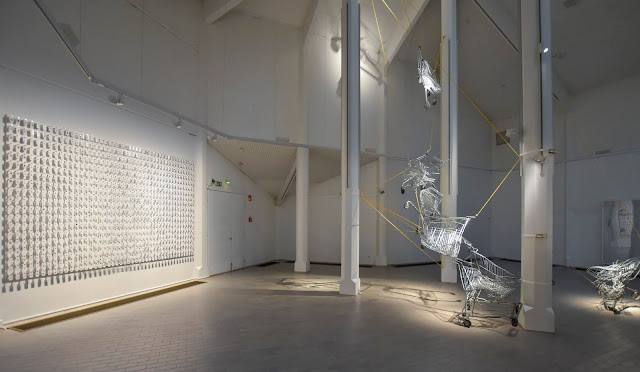 Kouvolan taidemuseon keskikerrokseen ripustetut taiteilija Timo Heinon teokset Yöportieri ja Addiktio. Yöportieri koostuu 879:stä alumiinikoukkuun ripustetusta valkoisesta narikkalapusta, jossa jokaisessa on eri ihmisen sormenjälki. Addiktio-teoksessa on seitsemän muotonsa menettänyttä ostoskärryä, jotka on ripustettu tilaan keltaisilla köysillä.