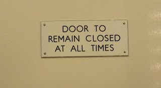A sign saying Door To Remain Closed At All Times