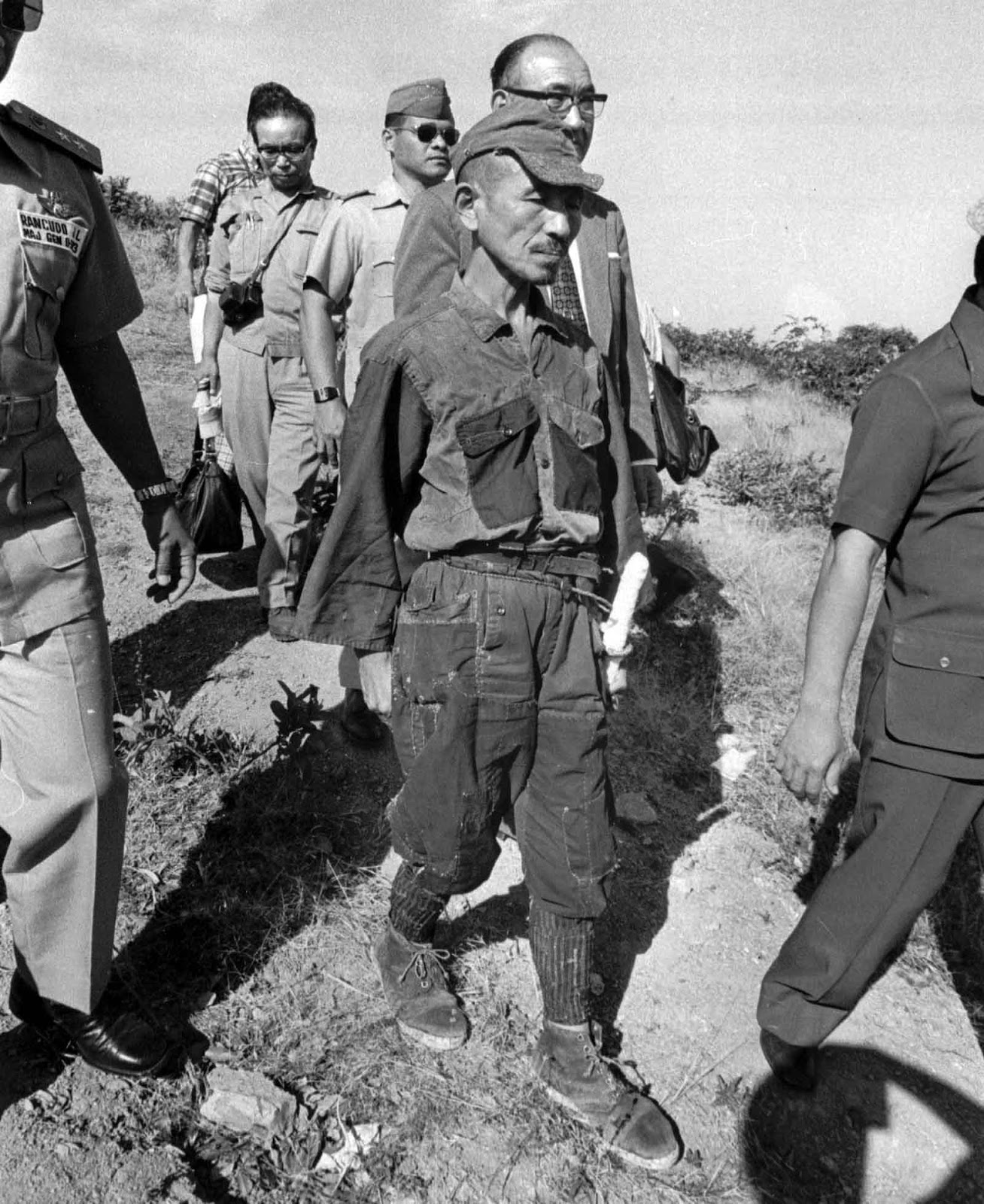 In this March, 1974 file photo, Hiroo Onoda, wearing his 30-year-old imperial army uniform, cap and sword, walks down a slope as he heads for a helicopter landing site on Lubang Island for a flight to Manila when he comes out of hiding in the jungle on the island, Philippines.
