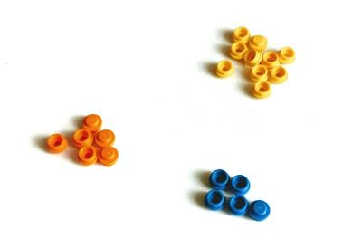 na zdjęciu trzy kupki okrągłych klocków Lego w trzech różnych kolorach