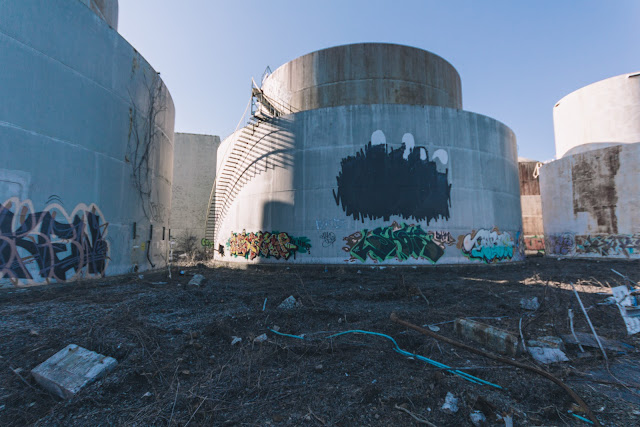 four graffiti covered oil tanks