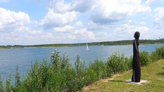 Das Foto zeigt den Zwenkauer See bei Leipzig bei Sonnenschein mit wenig Wolken. Ein weißes Segelboot ist auf dem See zu erkennen. Am Ufer wachsen Büsche und eine Holzskulptur in Form einer Frau ist zu erkennen.