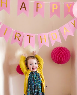 A blonde haired, blue eyed girl wearing a green floral dress and yellow cardigan has her hands above her head and pulled back slightly holding two white fluffy paper flower balls under a Happy Birthday banner in pink with two pink honeycomb structure decoration balls on the cream wall behind her.