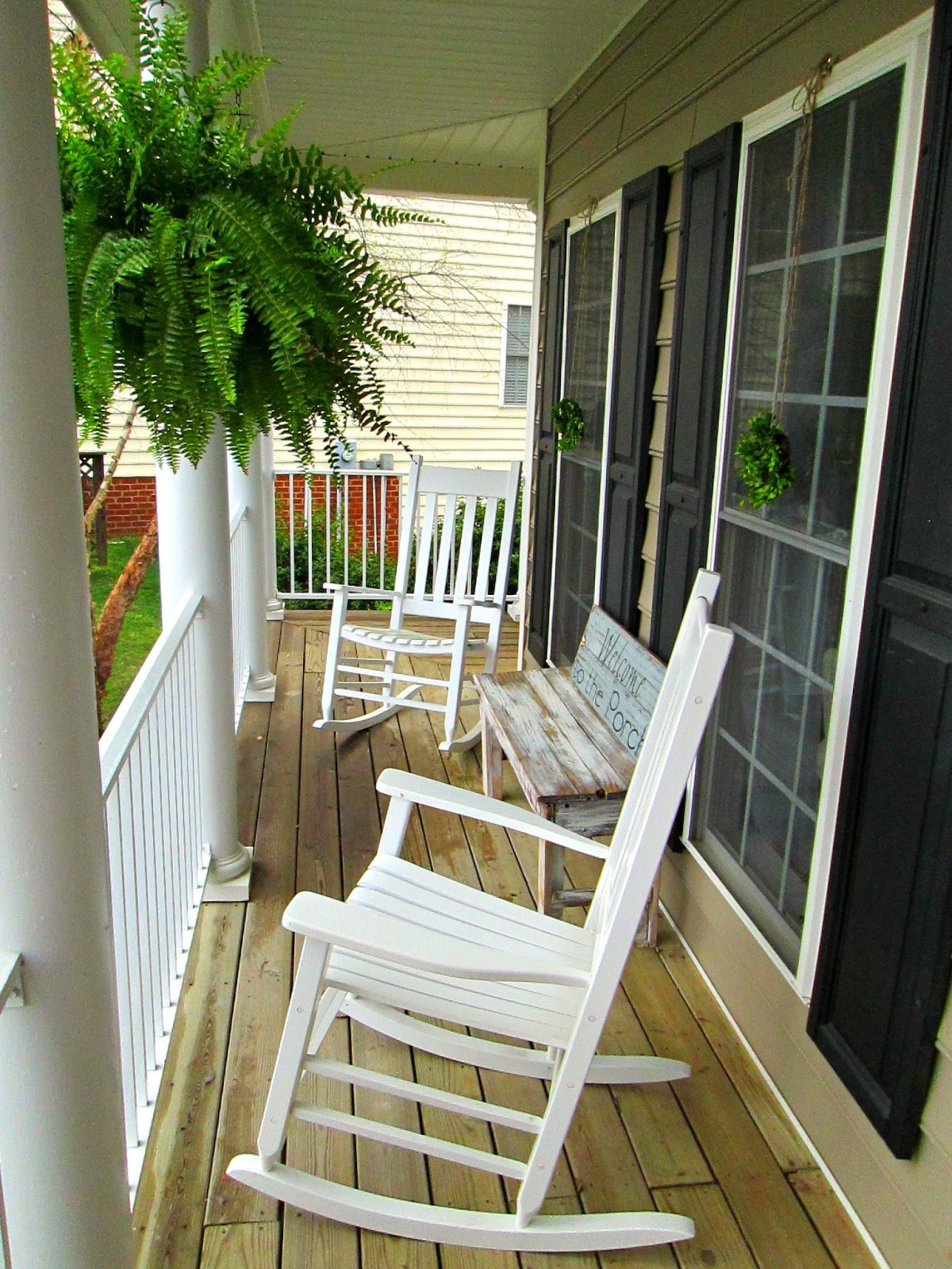 Down to earth style hanging ferns and wreaths for Long porch decorating ideas