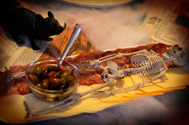 A meat and cheese platter with a skull on it and a bowl of olives.