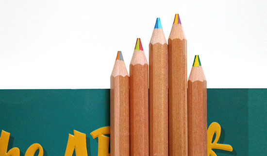 Pencils with multi-colored leads lined up along the top of a green book cover on a white background.