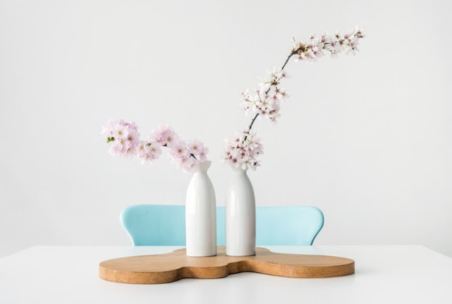 two white vase with pink flowers on a white table