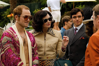 Taron Egerton in a fabulous purple robe as Elton John, Bryce Dallas Howard as his mother Sheila, and Richard Madden in a business suit as John Reid in the movie Rocketman