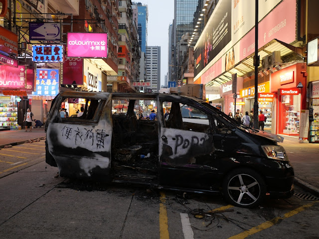 "burned vehicle with """"便衣狗車"" written on it"