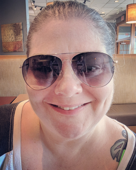 image of me from the shoulders up sitting in a restaurant smiling, with my hair pulled up into a bun, wearing sunglasses and a ringer tee with a white torso and grey arms