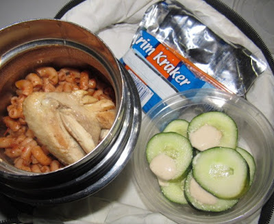 Nigerian school lunchbox meal of jollof macaroni with chicken and a side of cucumbers