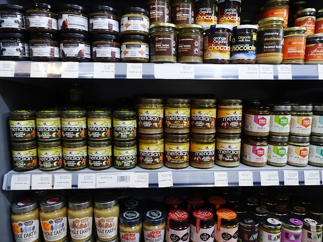 Different brands of nut butters on a shelf at food market
