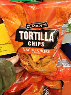 An unopened bag of Clancy's Nacho Cheese Flavored Tortilla Chips on an Aldi shelf, with my wife's arm reaching out to grab them