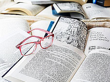 Lukutoukan tauolle jätettyjä avoimia kirjoja, joitten päällä silmälasit.