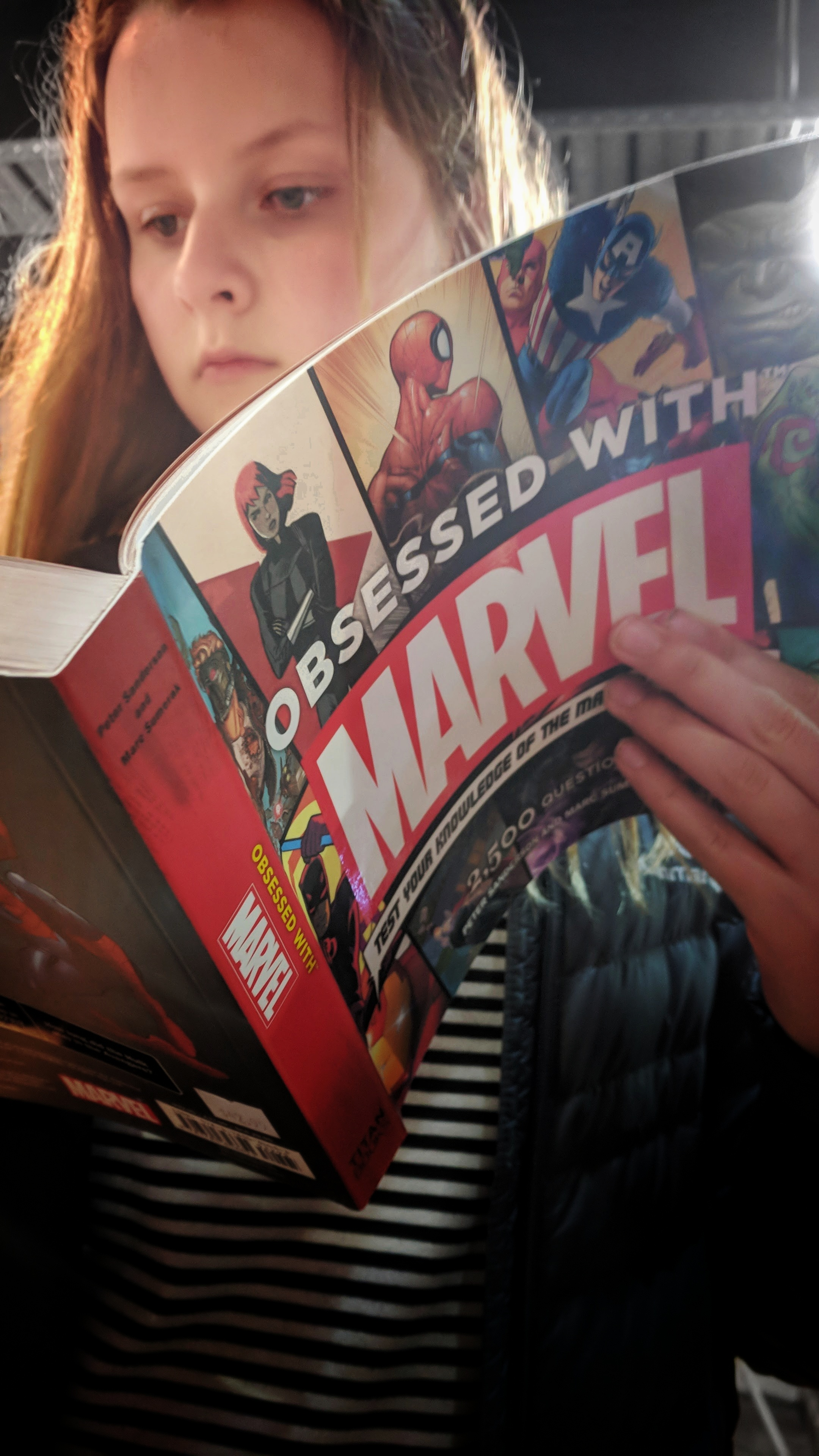 Girl reads 'Obsessed With Marvel' book