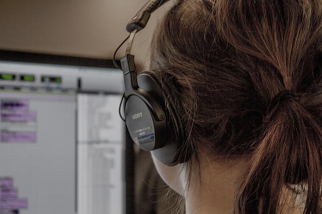 wanita yang menggunakan headset didepan komputer