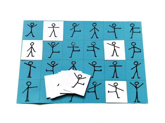 na zdjęciu niebieska plansza a4 z narysowanymi ludzikami w różnych pozycjach a na niej kilka kartoników w kolorze białym z ludzikami dopasowanymi do tych na niebieskiej planszy