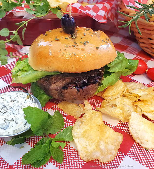 this is a lamb burger on a red checkerboard tablecloth along with potato chips and  with spinach tzatziki sauce