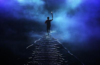 Άντρας με δάδα, τρέχει επάνω σε νερό. Ακολουθεί το κείμενο: Τιμή σε όσους στη ζωή, φυλάσσουν Θερμοπύλες. Γιατί εξηγούν τον Άνεμο, φωτώνουν το Σκοτάδι. Με Λογισμό και με Όνειρο, τριποδιστές του Φάους.   Γαιώνουν το Ουράνιο, στην άσωστην ζωή μας. ΕνΚαρδιώνουν Μάρτυρες, στηλογραφούν Διαθήκες. Διαβάζουν τα αξήγητα, ερμηνεύουν τα Μυστήρια. Σφραγίζουν φυλλάδια ναυτικά για ΑΛΑΡΓΙΝΟ ΛΙΜΑΝΙ.   ΣύνΕργοι των Μυσταγωγών, απάντων των Αιώνων. ΑναΒαθμώνουν το Κενό, χερσώνουν τας Αβύσσους. Λαλούν Ωδές ΑπώΓαιες, Σκάλες κρεμούν στον Θόλο. Γράφτουν Γραφές, Αδευτέρωτες, πανΆρχαιες Καινουργίες. Ιχνηλατούν το Όνειρο, αποστάζουν τον Αιθέρα.   Κερνούν με αχειροποίητους, τρισσοφεγγείς κρατήρες. Πόματα, αμεθυστικά, που ξεδιψούν Αιώνια. Χορδίζουν τις βροντόλυρες, με δοξαριές Ουράνιες. Για να ψωμίζονται οι Ευλογητοί, Σεπτοί, ΣυνΑδελφοί μας. Να π'ινουν απο ακένωτους Ηλιότευκτους κρατήρες. Άκρατους οίνους, αμέθυστους, που συνποσούν το ΣύνΠαν.   Αθροίζοντας του Μηδενός, τις λάγνες στρογγυλάδες. Κρεμάζοντας ατσαλόσκαλες, απ τις Κορφές του Θόλου. Απ όπου οι Μακάριοι, Μυσταγωγοί, Ψαλτάδες. Αιωρούνται μέσα στο Αβαρές, λογχίζοντας το Σκότος. Φωνίζοντες γραμματικών παμπάλαιων Κανόνες. Συλλαβικά ιερουργήματα, άηχες μελωδιές. Αρχαίες Ωδές, Αδευτέρωτες, Ποιητών Απαλαιώτων.   Φαεςφόρων ΗλιοΘηλαστών, Αρχίφωτων Μαστόρων.   Που καινουργούν το Άκτιστον, καταμεσής του Χάους..