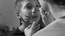 A child looking up while having face paint applied to their nose