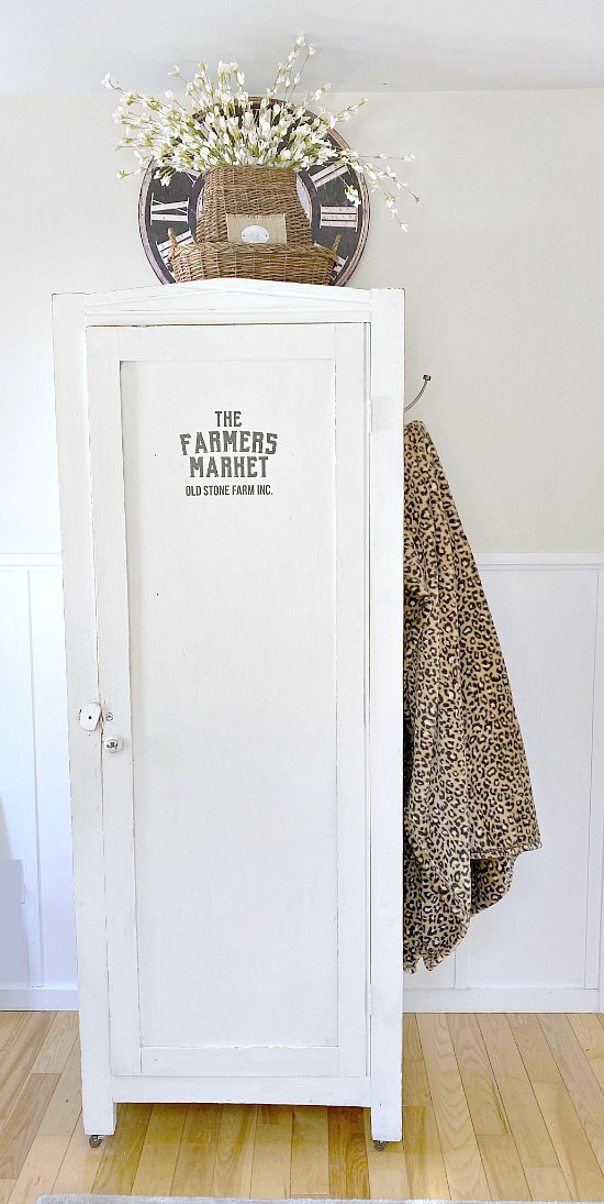 Finished white cupboard with hook and leopard throw.