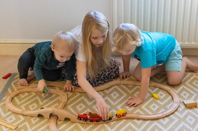 3 children playing with a wooden train set