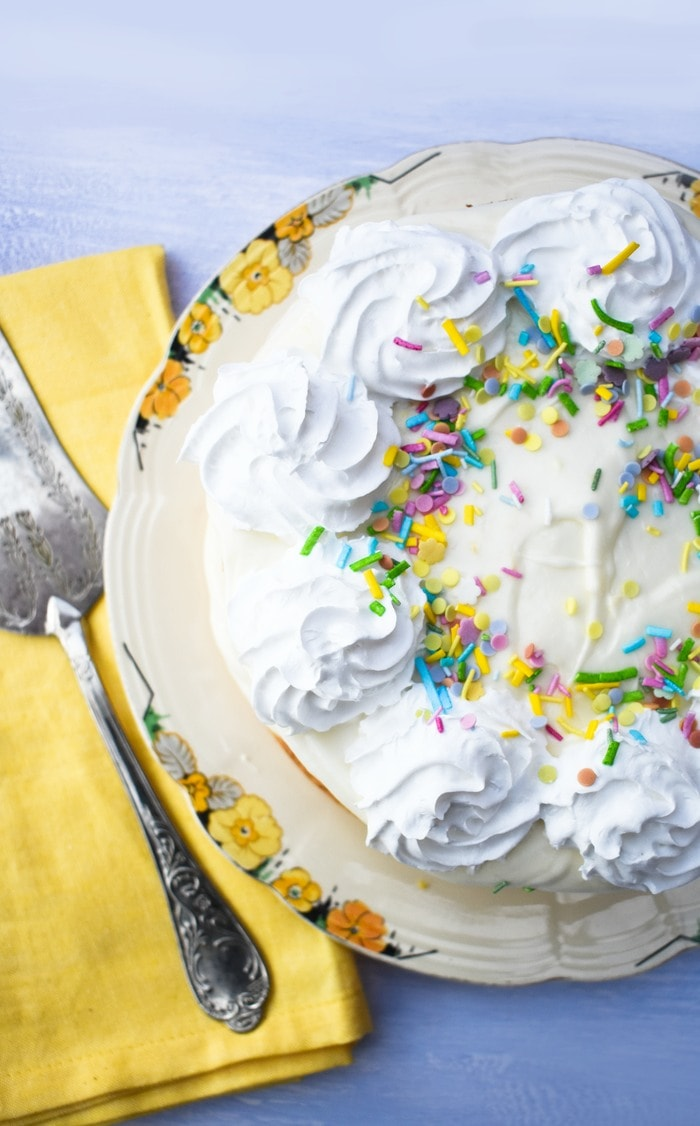 Quick vegan lemonade cake from above, topped with lemon buttercream, whipped cream and colourful sprinkles