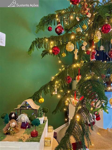 Uma árvore de natal enfeitada, com luzes acessas, e um presépio de bonequinhos de pano.