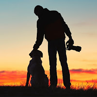 Silhouette of man with camera standing next to his dog