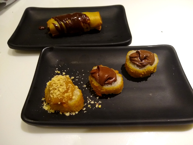 A huramaki filled with chocolate and three deep fried banana sushis, one with dulce de leche and the other with nutella.