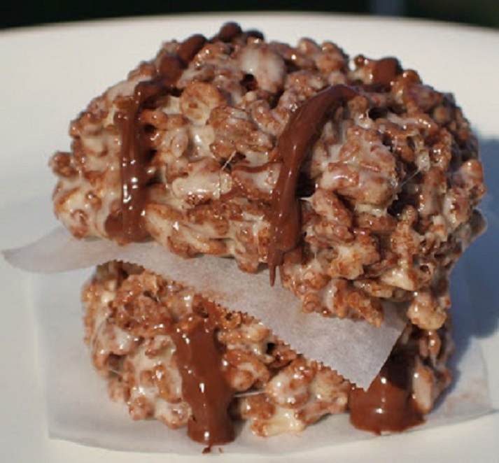 These are a bar cookie no bake with chocolate rice krispies, marshmallow and Nutella drizzled over the topped. They are layered bars on top of each other with wax paper in between them on a white plate