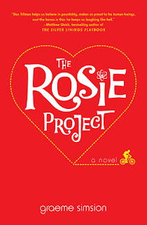 """Rosie Project book cover (the """"i"""" in """"Rosie"""" is dotted with an atom, as a man on a bicycle rides in a heart-shaped line around the title, on a solid red background)"""