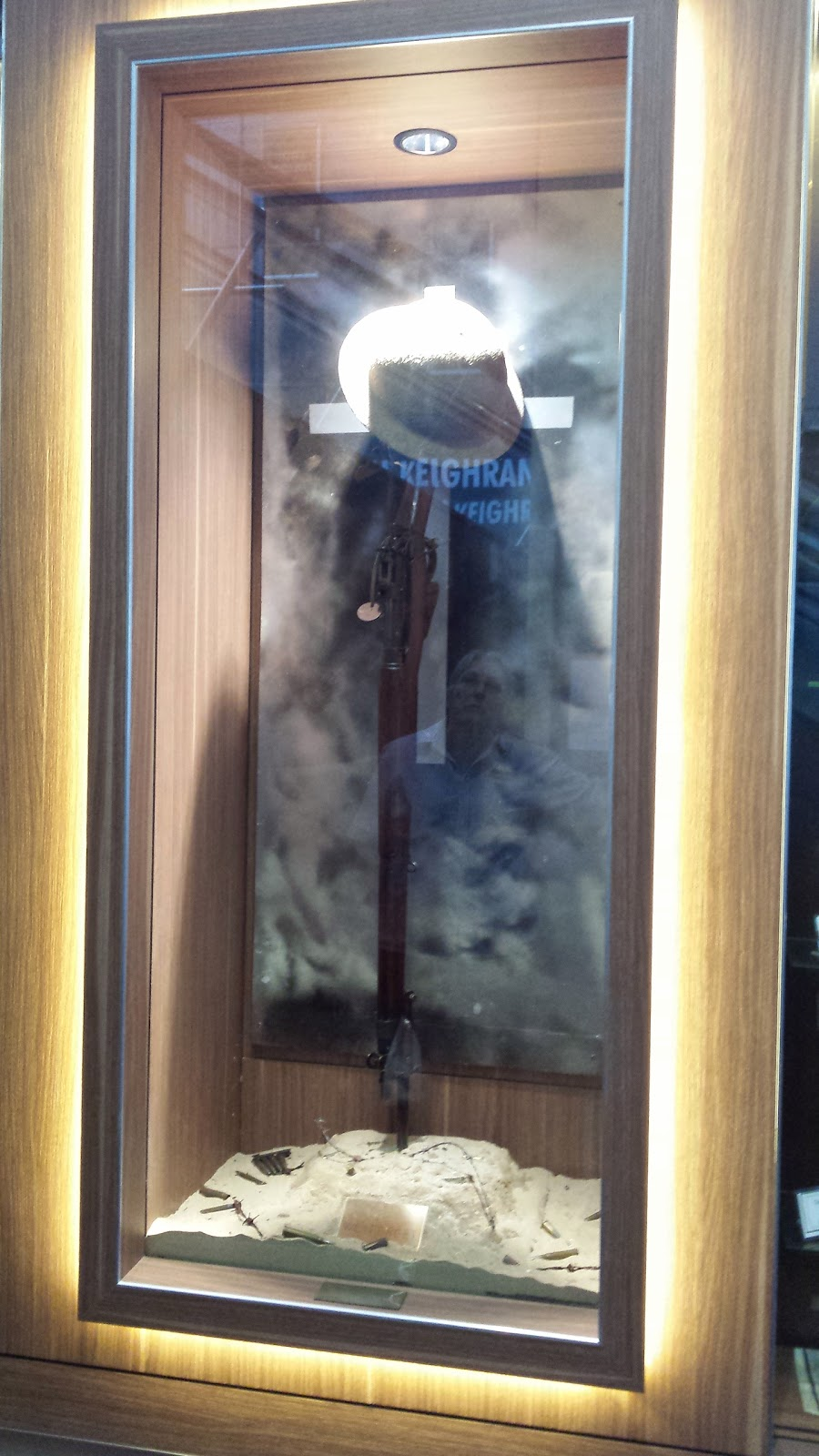 display case at RSL Museum Redcliffe featuring rifle and hat propped in bed of sand with bullets in front of cross