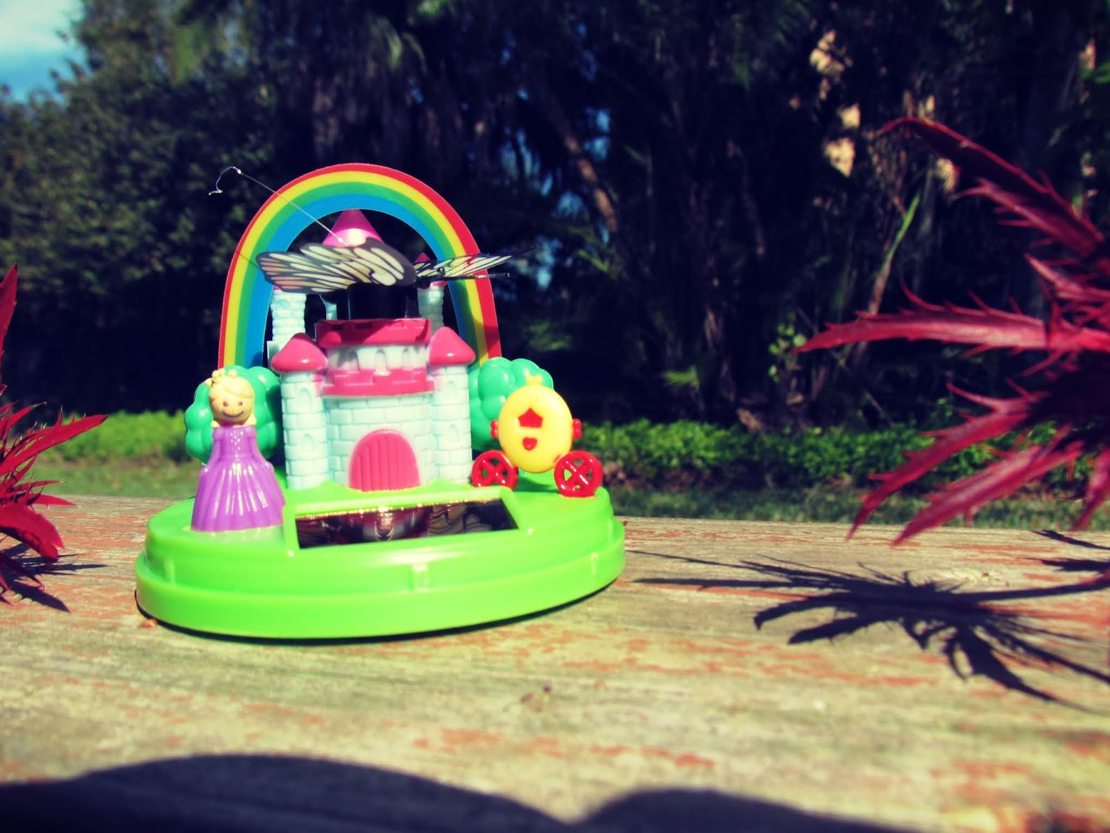 A magical fairy castle and princess diorama and microdome for the garden moves in sunlight in the backyard and wooden patio setting