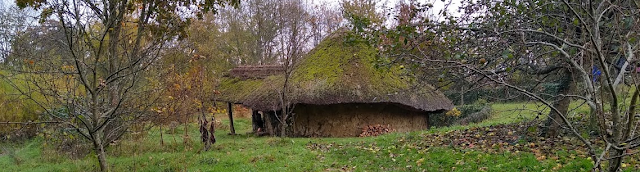 View of a reconstructed Iron Age round house with bare winter trees around.