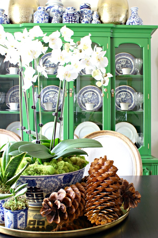 orchid centerpiece, sugar pine cones, blue and white pottery, brass tray, vintage furniture