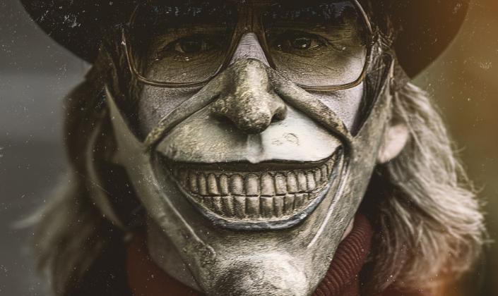 Imagem de capa: poster com o personagem sequestrador, usando uma máscara prateada com um sorriso de dentes cinzentos, um par de óculos por trás de um rosto pintado, nariz falso, longos cabelos e uma cartola preta, encarando algo em sua frente.