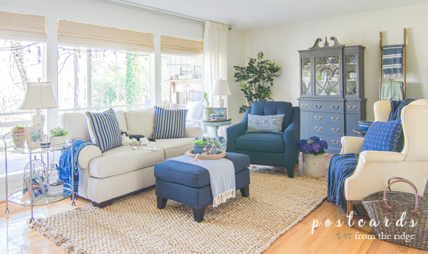 cozy blue and white furniture in living room with large windows