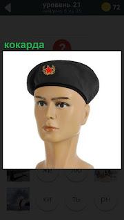 На голове манекена одет берет, на котором имеется кокарда