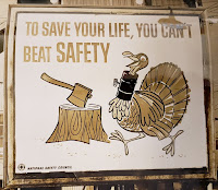 Poster shows tree stump with ax stuck in it and a turkey with a metal pipe protecting its neck. Text reads: To Save Your Life, You Can't Beat Safety
